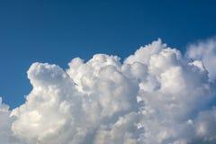 Ljusa soliga moln mot blå himmel för middagar royaltyfri foto