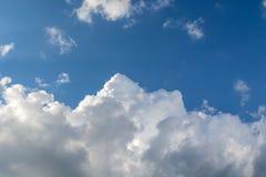 Ljusa soliga moln mot blå himmel för middagar arkivfoton