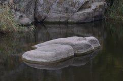 Ljusa stenblock i en mörk flod Säng för sagolika sjöjungfruar royaltyfria foton