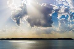Ljusa strålar för soluppgång/för solnedgång över sjön arkivbilder