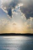 Ljusa strålar för soluppgång/för solnedgång över sjön fotografering för bildbyråer
