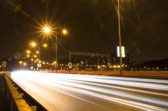 Ljusa strimmor för bil på en bro över den Vltava floden i Prague på natten Royaltyfri Bild