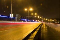 Ljusa strimmor för bil på en bro över den Vltava floden i Prague på natten Fotografering för Bildbyråer