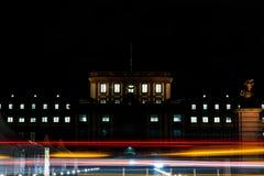 Ljusa strimmor och rörelse på natten framme av det Mannheim universitetet Arkivfoton