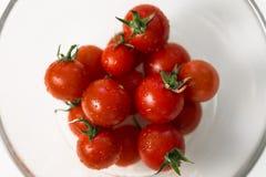 Ljusa tomater i en glasföremål Arkivbild