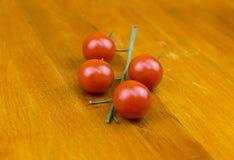 Ljusa tomater på en filial ligger på ett bitande träbräde Royaltyfri Foto