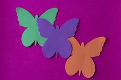 Ljusa tre och färgade fjärilar som göras av mjukt material på en fuchsiatrasabakgrund royaltyfria bilder
