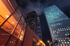 Ljusa upplysta ckyscrapers under natthimmel Arkivbilder