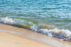 Ljusa vågor som tvättar sig upp på en guld- sandstrand arkivfoto
