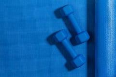 Ljusa vikter överst av yogamadrassen Öva sund livsstilbakgrund royaltyfri foto