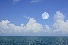 Ljusa vitmoln och månen i blå himmel över det gröna havet Royaltyfri Foto