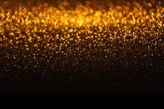 Ljusbakgrund, abstrakt guld- suddighetsferieljus som är guld- Arkivfoto