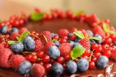 Ljusbrun kaka med härliga den bärjordgubbar, hallon, blåbär, vinbäret och mintkaramellen Arkivfoto