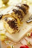 Ljusbrun rulle för traditionell jul med chokladpralin, chokladchiper och guld- stjärnor på ferietabellnärbilden royaltyfri fotografi