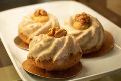 Ljusbruna muffin med karamellsirap och muttrar arkivbild