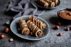Ljusbruna rör som fylls med hasselnötkräm och chokladtoppning Royaltyfria Foton