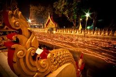 Ljuset från stearinljuset tände på natten runt om kyrkan av buddistfastlagen Arkivbild