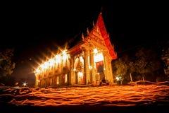 Ljuset från stearinljuset tände på natten runt om kyrkan av buddistfastlagen Fotografering för Bildbyråer