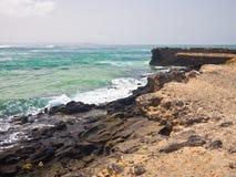 Ljusgrön havbränning och stenig kust Arkivbilder