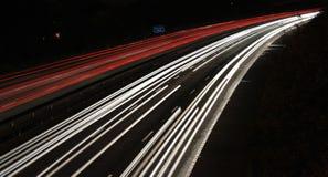Ljusslingor av annalkande bilar på natten Arkivbild