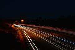 Ljusslingor av bilar på huvudvägen Arkivbild