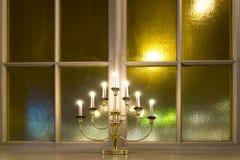 Ljusstake på fönsteravsatsen Fotografering för Bildbyråer