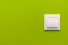 Ljusströmbrytare på den gröna väggen med dekorativ murbruk Royaltyfria Foton