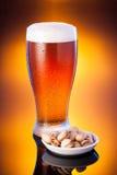ljust öl i frostigt exponeringsglas med pistascher över ljus bärnstenbac arkivbilder