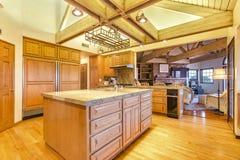 Ljust, öppet och varmt kök med välvd tak och ö w arkivfoton