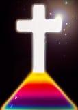 Ljust argt kristendomensymbol med regnbågebanan till korset Arkivfoto