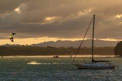 Ljust avbrott för solnedgång till och med stormiga moln över fjärden arkivbilder