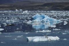 Ljust - blåa isberg på lagun för glaciär för ³ n för Jökulsà ¡ rlà med mörkare skuggat vatten, Island royaltyfri foto