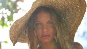 Ljust - den bruna haired flickan i hatten på stranden visar en kyss arkivfilmer