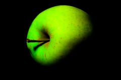 Ljust - det guld- gröna äpplet - läckert ligga på dess sida på en svart bakgrund som är upplyst vid det vänstert Royaltyfri Foto