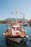 Ljust färgad blå och röd fiskebåt i hamn Royaltyfri Foto