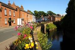 Ljust färgade blom- korgar i den nätta engelska blom- byn av Croston Royaltyfria Bilder