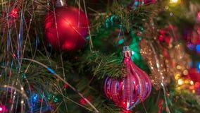 Ljust färgade glade julgranprydnader hängde upp med ljus och glitter arkivbild
