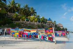 Ljust färgat tyg som är till salu på en vit sandstrand mot en härlig blå himmel Arkivbilder