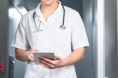 Ljust foto av den manliga doktorn i likformig med stetoskopet som kommer ut ur hissen och använder datorminnestavlan i sjukhus royaltyfri fotografi