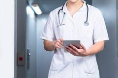 Ljust foto av den manliga doktorn i likformig med stetoskopet som kommer ut ur hissen och använder datorminnestavlan i sjukhus arkivbilder