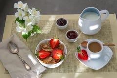 Ljust frukostkaffe med mjölkar och mysli, nya jordgubbar, driftstopp arkivbild