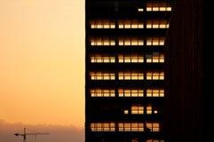 Ljust gå för solnedgång till och med skelettet av demonterad byggnad Deconstruction av den gamla kontorsskyskrapan Royaltyfri Bild