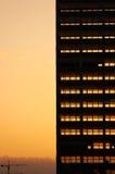 Ljust gå för solnedgång till och med skelettet av demonterad byggnad Deconstruction av den gamla kontorsskyskrapan Arkivbild