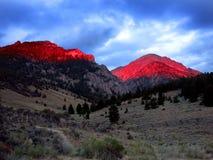 Ljust glöda för bergsolljussolnedgång rött Arkivbild