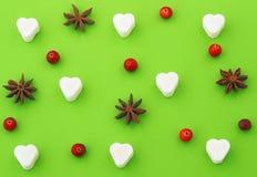 Ljust - grön bakgrund med sockerhjärta, anisstjärnor och tranbär Royaltyfri Bild