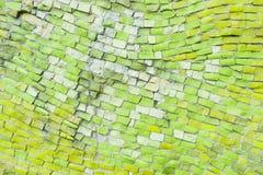 Ljust - grön yttersida av den gamla smula abstrakta dekorativa mosaiken som bakgrund Mångfärgade keramiska stenar på väggbyggnad arkivfoton