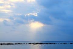 Ljust guld- vitt solljus som kommer till och med moln och faller över oändligt havsvatten på horisonten - abstrakt naturlig bakgr arkivbilder