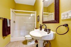 Ljust gult badrum med den glass dörrduschen Fotografering för Bildbyråer