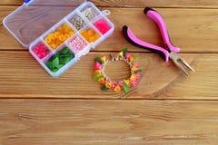 Ljust härligt handgjort armband Plattång Boxas med pärlor, plast-blommor och tillbehör för handgjorda smycken arkivbilder