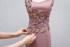 Ljust - handgjort hänga för rosa formgivarekvinnors klänning på en vit skyltdocka med en prydnad av guld-, gråa och rosa pärlor i royaltyfri foto